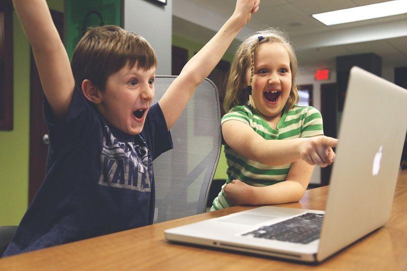 photo of a boy and girl enjoying something on a laptop