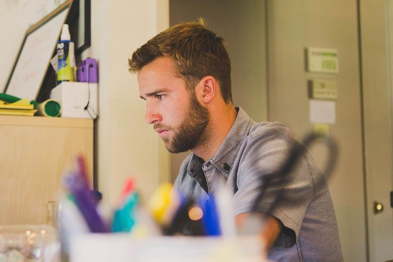 photo of young man at work in office