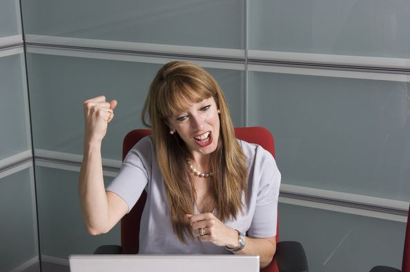photo of lady celebrating win behind laptop