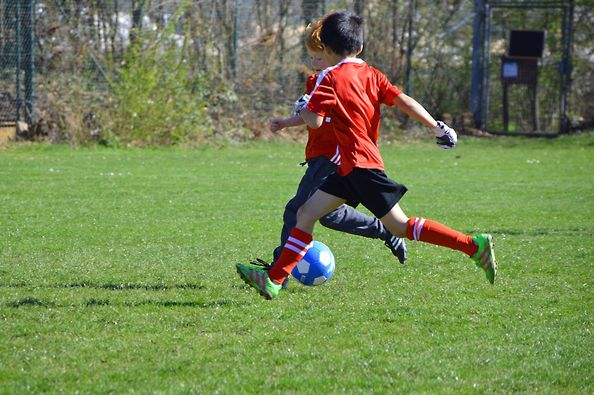 photo of two boys playing soccer